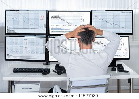 Trader With Hands On Head Looking At Graphs On Screens