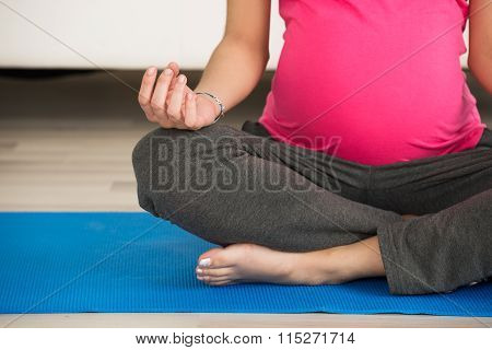 Pregnant Woman Doing Yoga On Exercise Mat At Home