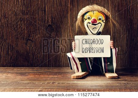 closeup of an old marionette with its face painted as a sad clown holding a signboard with the text childhood depression