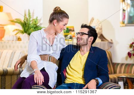 Young couple selecting together armchair in furniture store  poster