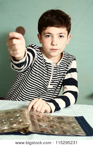 boy preteen numismatic collector show his coin with hole in the middle look through it close up portrait poster