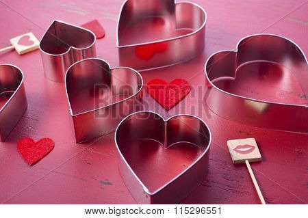 Heart Shaped Cookie Cutters on a rustic red wood table background. poster