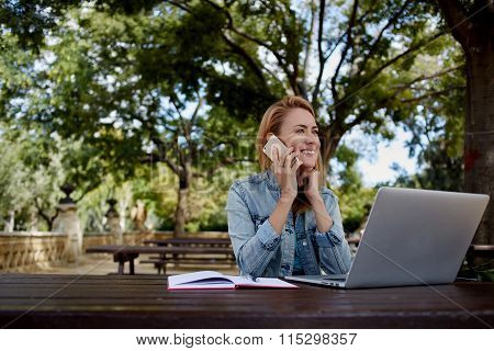 Happy female talking with her boyfriend on cell telephone while relaxing outdoors