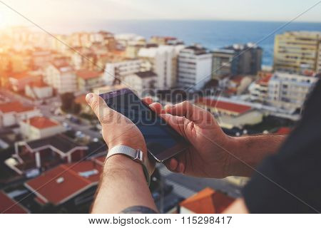 Young male chatting on cell telephone while looking on city from building's high floor
