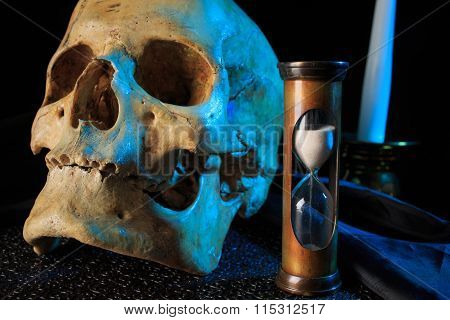 human skull on a book next to the clock. concept of black magic