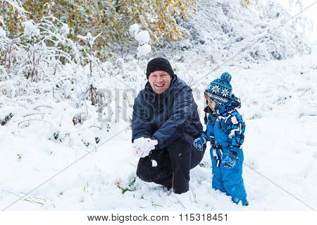 Happy child and dad having fun with snow in winter