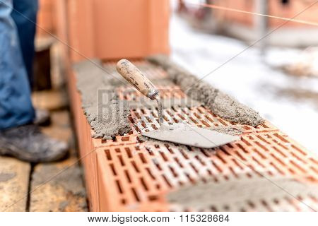 Detail Of Construction Site, Trowel Or Putty Knife On Top Of Brick Layer