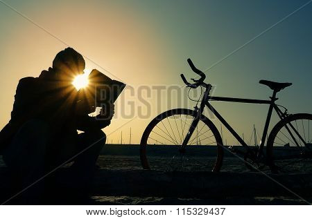 Man With Bike Silhouette - Senior Reading On The Beach At Sunset - Hipster Guy With Bycicle Sitting