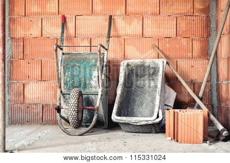 Brick Layering With Mortar, Wheel Barrow And Cement Mixer On Construction Site