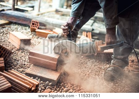Industrial Construction Worker Using A Professional Angle Grinder For Cutting Bricks