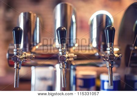 Beer Tap At Restaurant, Bar Or Pub. Close-up Details Of Beer Draft Taps In A Row