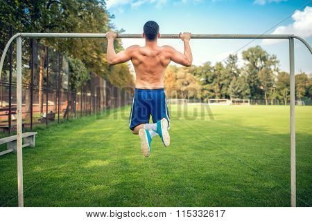 Sexy Bodybuilder Working Out In Park, Doing Chin Ups And Push Ups. Male Fitness Player Training Outd