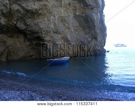 Beach sea shore with rocks, waves and sailing ships from Amalfi region in Italy