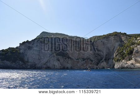 Rocky shoreline and boats of the Mediterranean Sea in Greece