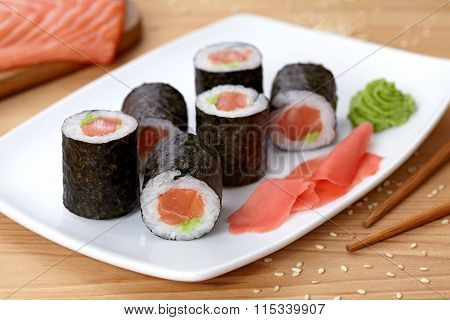 Maki sushi roll with salmon, wasabi, ginger and nori seaweed.
