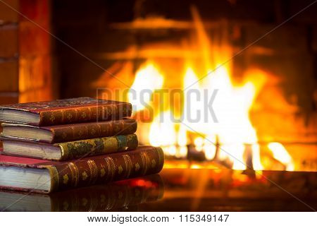 Antique books in front of warm fireplace. Magical relaxed cozy atmosphere near fire.