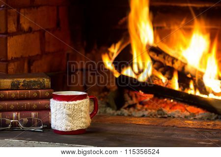 Cup of hot drink, antique books and fireplace as background. Christmas or winter warming drink