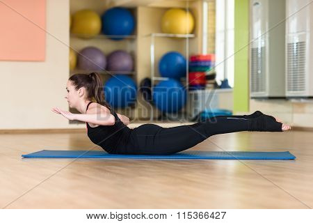 Young athletic woman doing yoga pose in bhanga Asana Cobra Pose. Indoor gym. poster