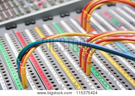 Patch Cables On A Studio Mixer With Blurry Background poster