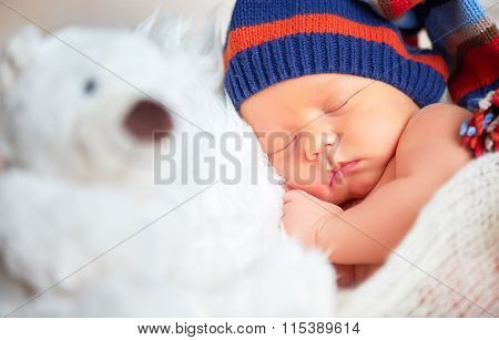Newborn Baby In Knit Cap And Teddy Toy Bear Sleeping