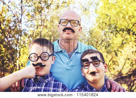 a dad with his sons all acting goofy wearing mustaches during a summer day toned with a retro vintage instagram effect app or action