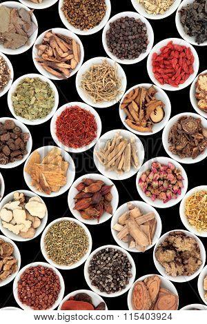 Chinese herbal medicine ingredients in porcelain bowls over black background.