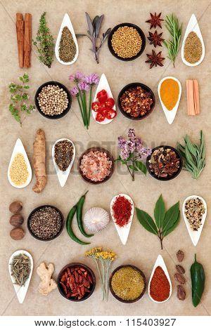 Spice and herb food seasoning sampler over natural hemp paper background.