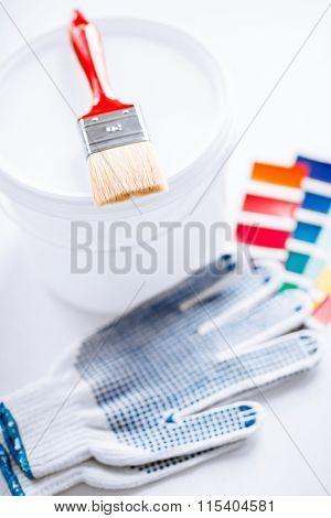 paintbrush, paint pot, gloves and pantone samples