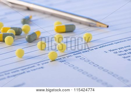 Pen and some medicines on top of hospital form.