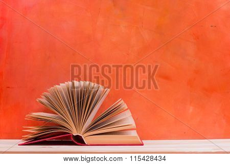 Composition with vintage old hardback books, diary, fanned pages on wooden deck table and red background. Books stacking. Back to school. Copy Space. Education background poster