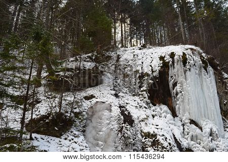 Small mountain waterfall frozen in the middle of the winter