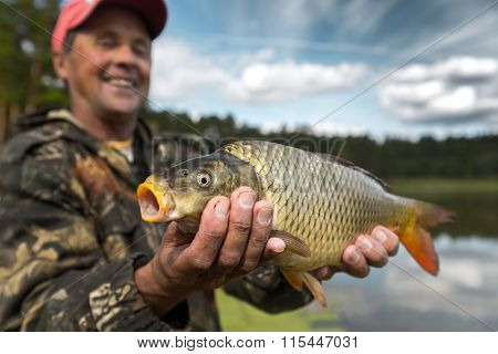 Happy smiling fisherman holding his trophy carp (Cyprinus carpio) with lake on the background. Focus on the fish