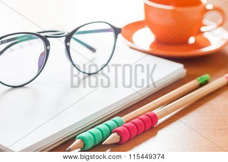 Pencils And Eyeglasses On Open Blank White Notebook With Coffee Cup On The Desk