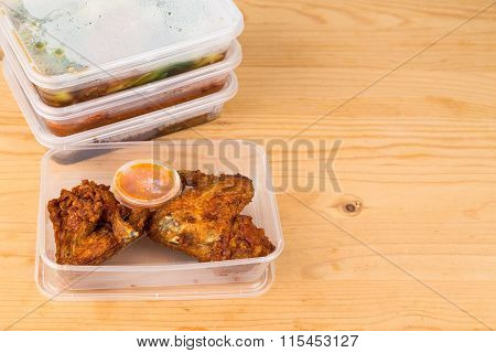 Convenient but unhealthy disposable plastic lunch boxes with take away meal on wooden table poster