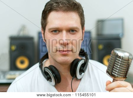 Young male sound producer in recording studio.