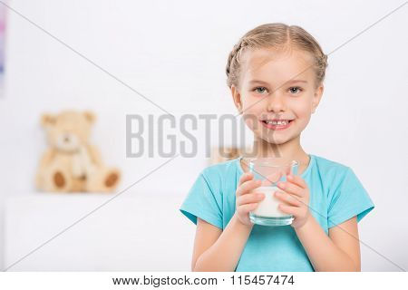 Smiling child is holding a glass of milk.