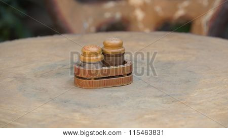 Salt-cellar and pepper-caster on outdoors table in cloudy day