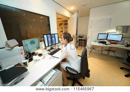 Experienced doctor looking at MRI scan of lumbar region on Monitor in control room