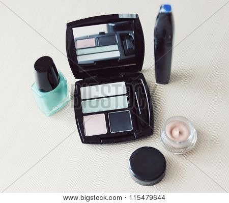 Set of eyeshadow, mascara, primer, turquoise blue nail polish and other cosmetics on a dressing tabl