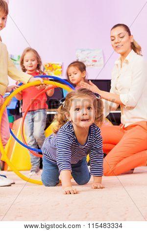 Girl go though hoops playing game in kindergarten