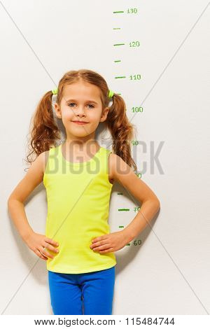 Little girl stand by measuring height scale