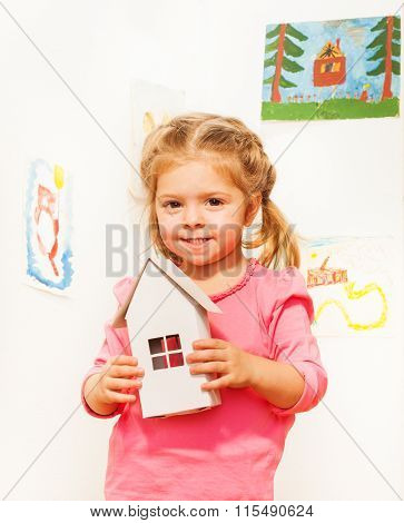 Smiling little girl handling cardboard white small doll house at her hands among beautiful paintings