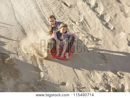 Adventuresome girls boarding down the Sand Dunes