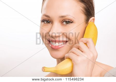 Young girl with banana beside her face.