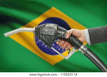 Fuel Pump Nozzle In Hand With National Flag On Background - Brazil