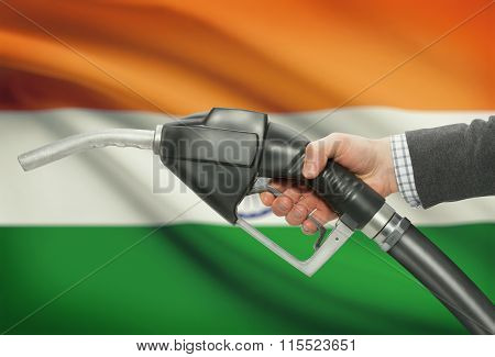 Fuel Pump Nozzle In Hand With National Flag On Background - India