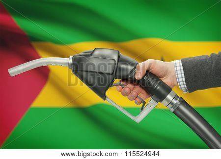 Fuel Pump Nozzle In Hand With National Flag On Background - Sao Tome And Principe