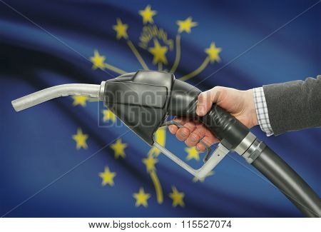 Fuel Pump Nozzle In Hand With Usa States Flags On Background - Indiana