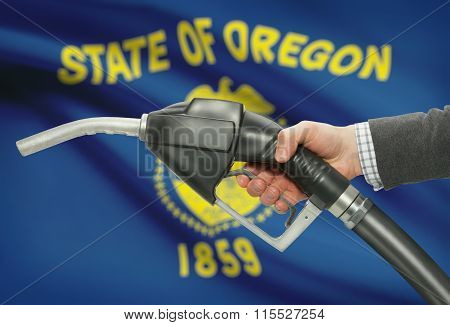 Fuel Pump Nozzle In Hand With Usa States Flags On Background - Oregon