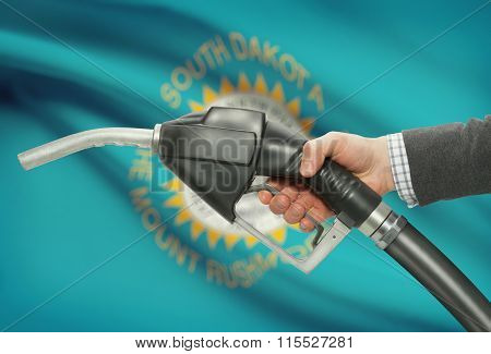 Fuel Pump Nozzle In Hand With Usa States Flags On Background - South Dakota